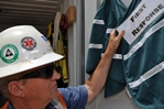 Batch plant Superintendent Rich Hamilton's hard hat bears both the original first responders' logo (left) and the current emblem. The stickers indicate authorization to be at an incident site; all others must stay clear.