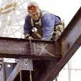 A picture of a construction worker welding together steel beams from high above the ground.
