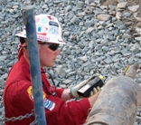 An oil and gas emegency planner takes air samples at the test valve to determine whether hydrogen sulfide is present during drilling operations.