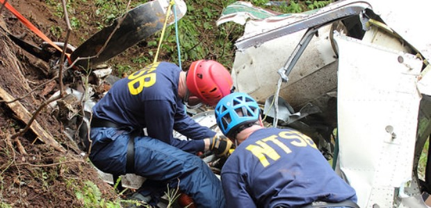 This June, 30, 2015, photo shows NTSB Investigators Brice Banning and Clint Crookshanks examining wreckage from the aircraft  that had crashed five days earlier near Ketchikan, Alaska. (NTSB photo by Ketchikan Volunteer Rescue Squad – Jerry Kiffer)