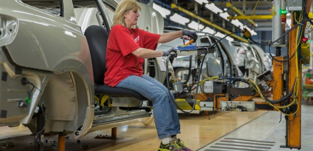 Autoworkers at the Lansing plant use the Ergo Chair to finish work in the rear of the Chevrolet Traverse with tools and parts alongside, at the right height for their work, according to GM.