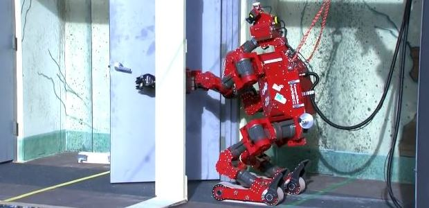 Carnegie Mellon University-NREC designed CHIMP (CMU Highly Intelligent Mobile Platform) is shown during the 2013 DARPA Robotics Challenge Trials task of opening a series of doors. CHIMP finished third in the trials. (DARPA image)