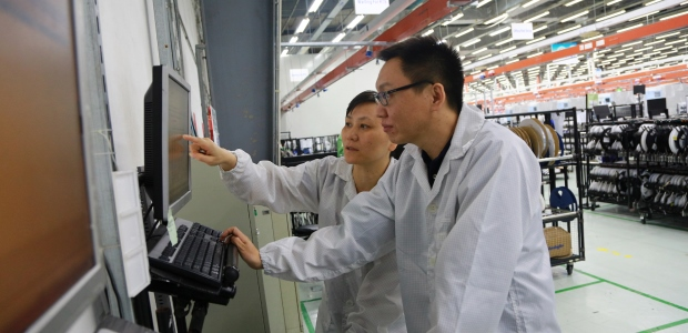 "Tan Huan (front), section manager of Planning, and Dai Lan, Inventory Control manager, confer while working in the Jabil Shanghai facility. ""This improvement has solved the problem of low efficiency and human error that we previously experienced with paper-based systems,"" Dai Lan said. ""The shift from manual to system control of materials provides a clear, accurate status for the plant."""