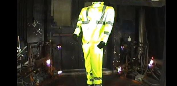 This image is a screen capture from a 2013 Bulwark video showing an arc and flash fire rated rain suit being exposed to a three-second flash fire. The test method depicted in the video is ASTM F 1930, which is the flame exposure test used in NFPA 2112 and ASTM F 2733.