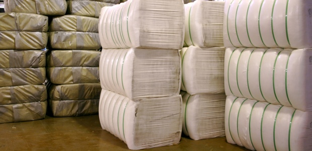 Huge bales of fiber—from 400 to 700 pounds each, depending on the fiber—are delivered to a yarn plant for processing. (TenCate Protective Fabrics photo)