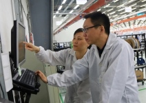 Tan Huan (front), section manager of Planning, and Dai Lan, Inventory Control manager, confer while working in the Jabil Shanghai facility. (Jabil Inc. photo)